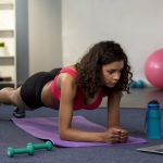 Mixed Race Young Woman Doing Online Workout In Front Of Laptop,